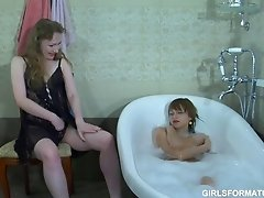 Two horny lesbians play with each others muff in bathroom